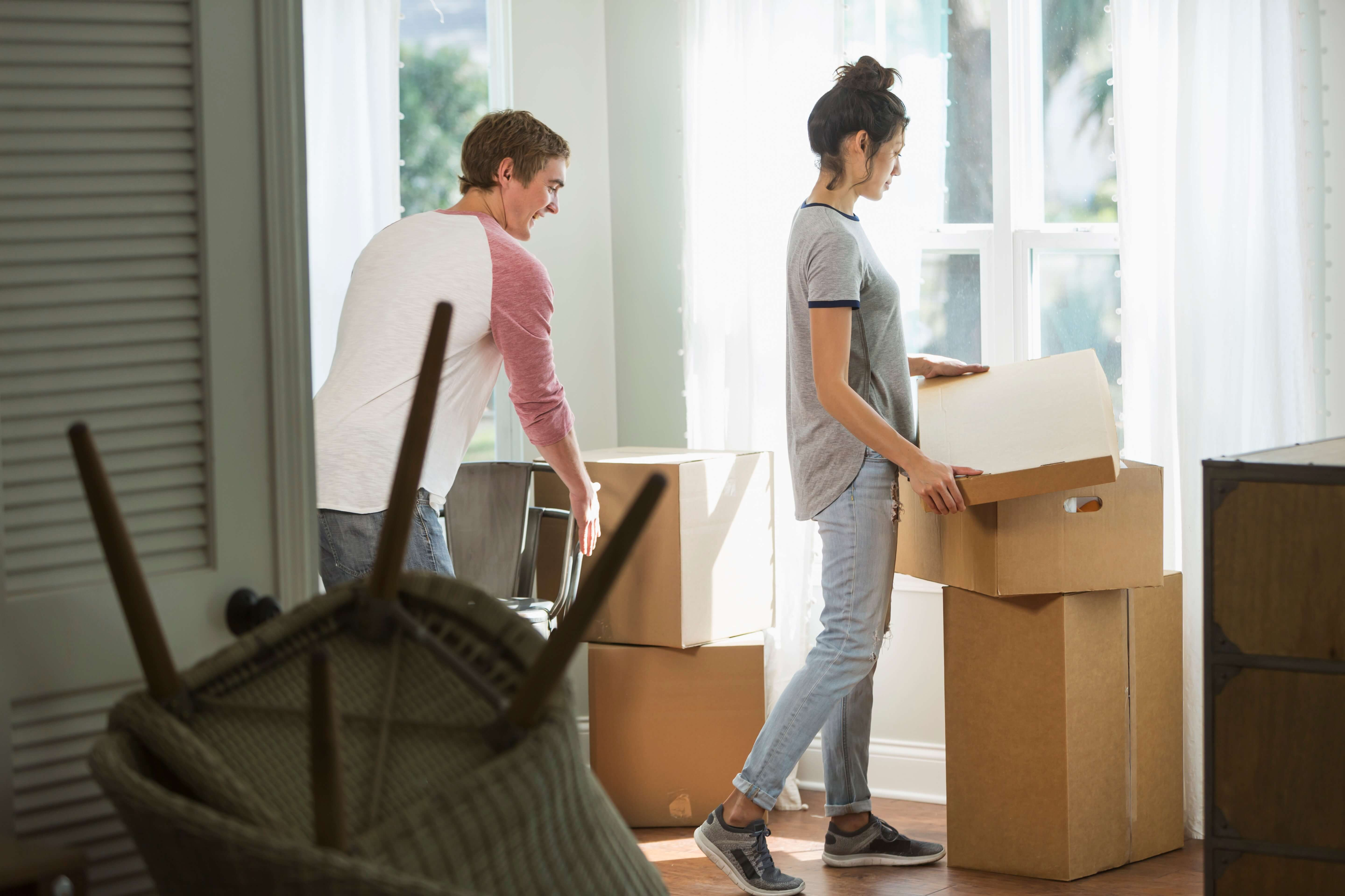 A young couple moving into their new home, carrying boxes.