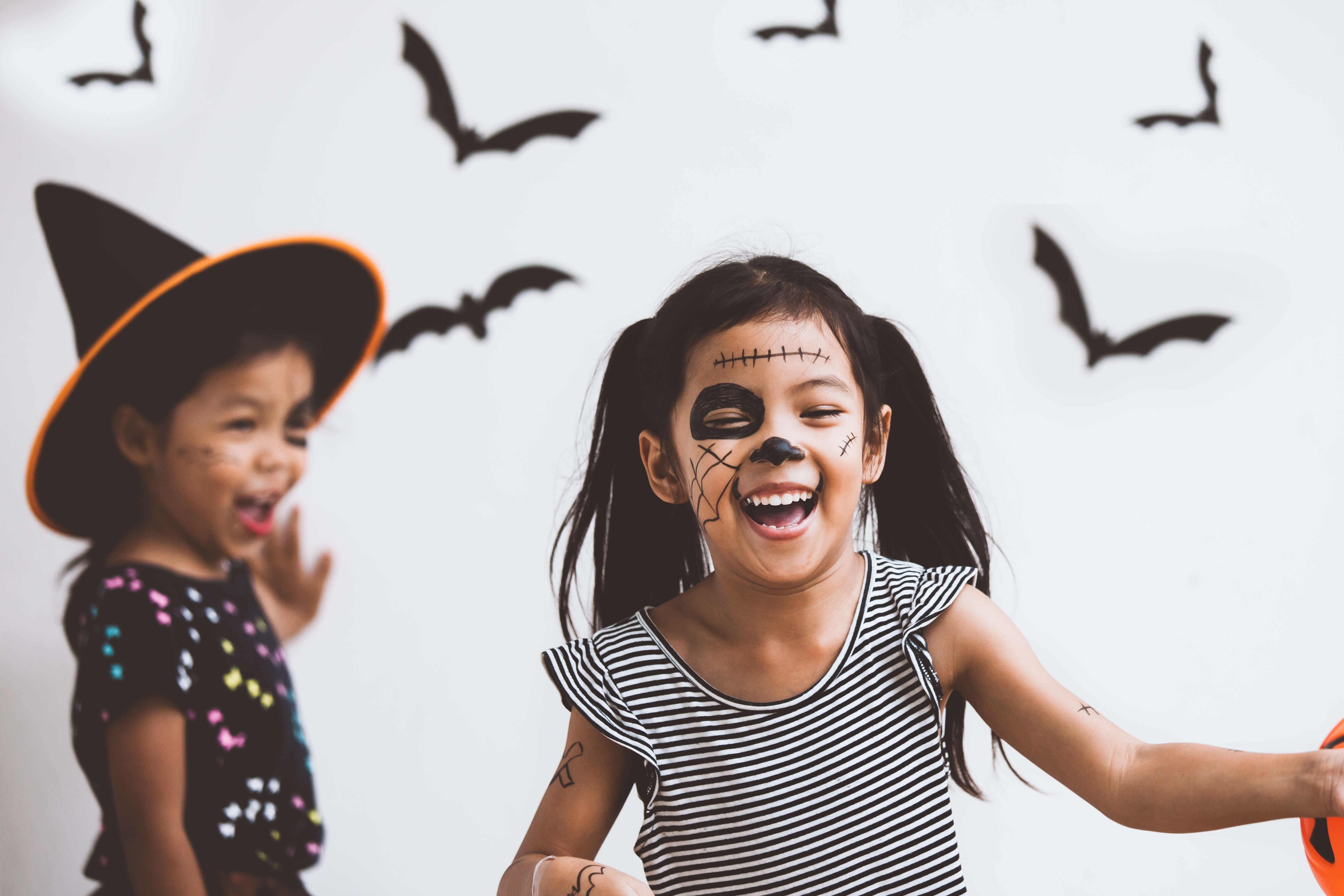 Young children dressed in halloween costumes, playing and laughing.
