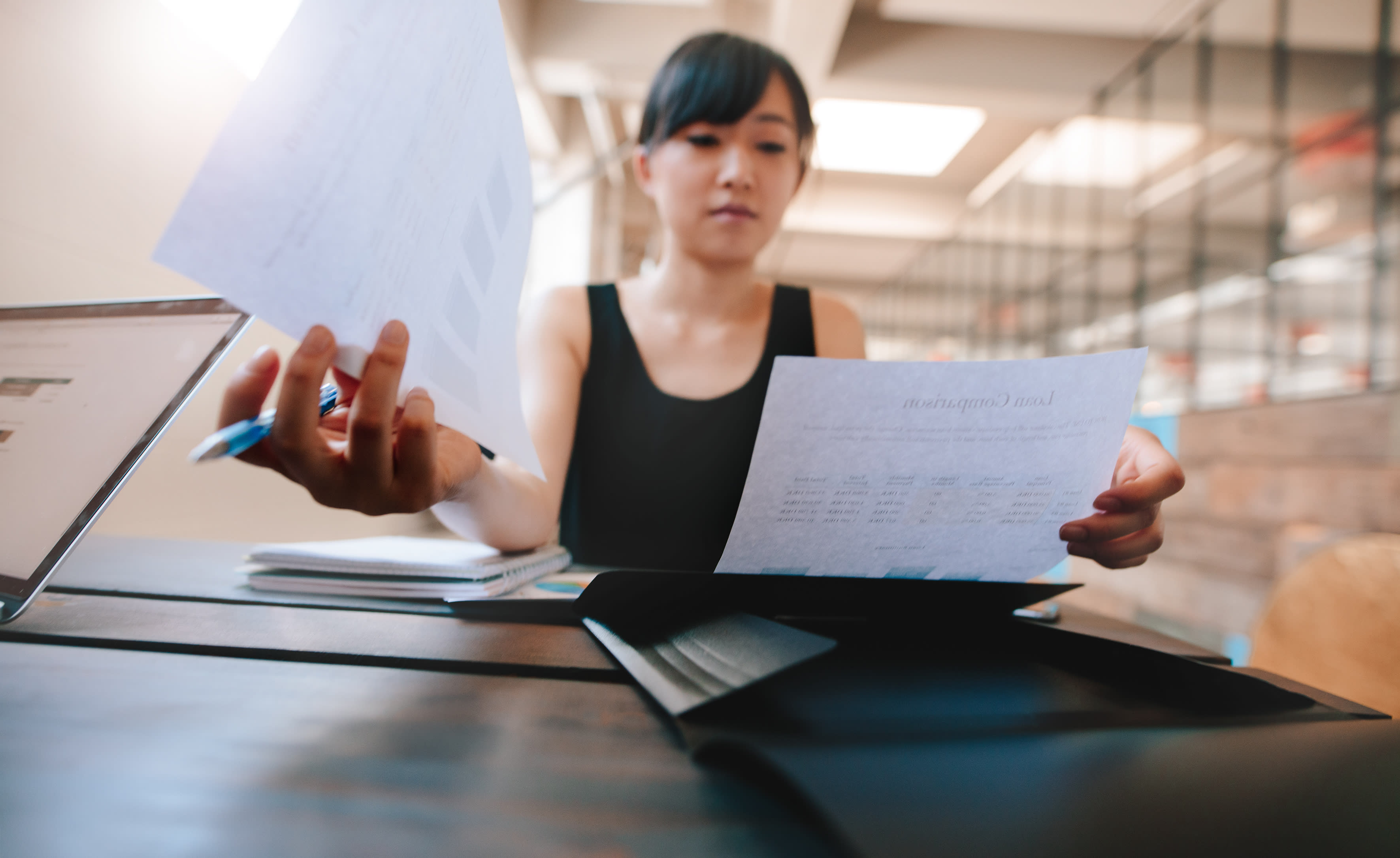 Shot of woman sitting at her desk and going through documents. Asian businesswoman with paperwork in office.