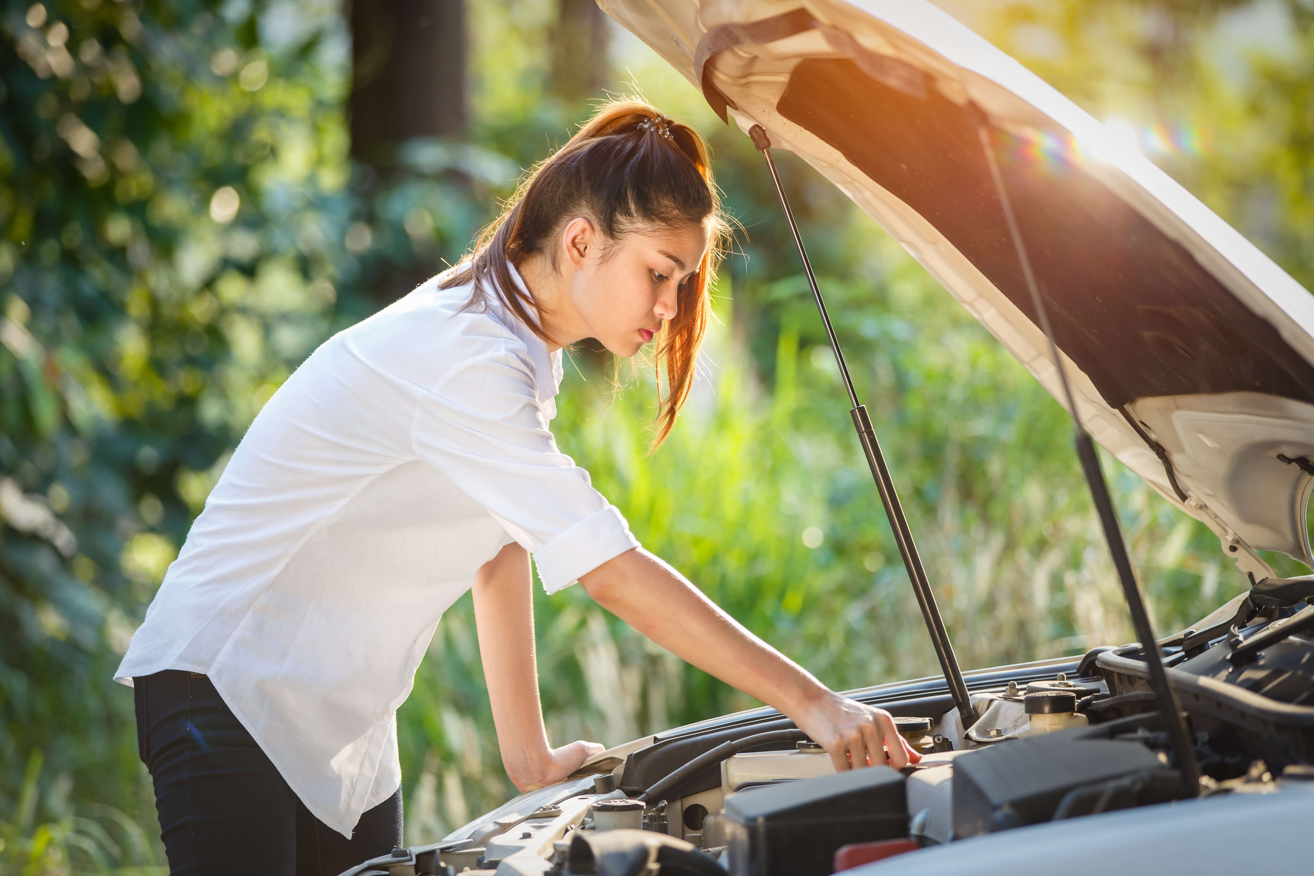 A young woman checking he engine of her car.