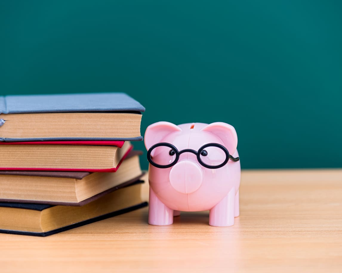 A piggy bank and stack of books.