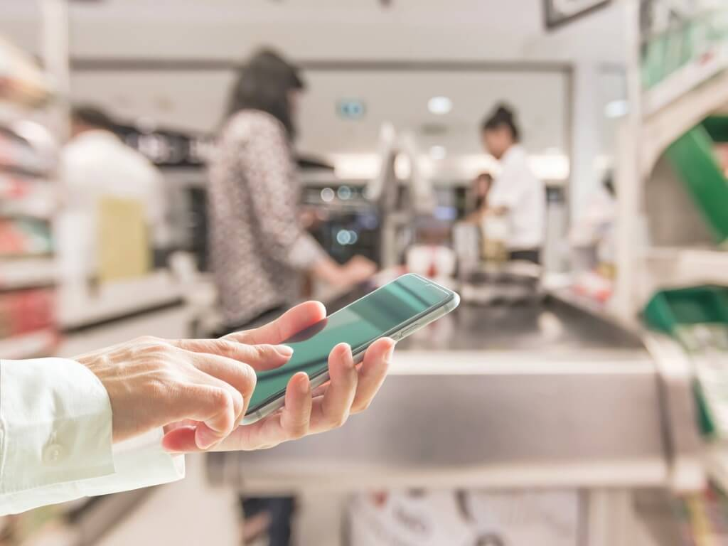 A person looking at a budget app on their phone at the check-out counter of a store.