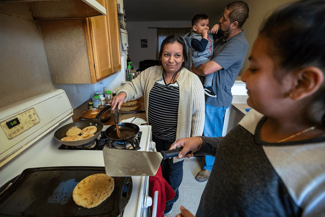 Woman prepares pancakes with her daughter; her husband and son play in the background.