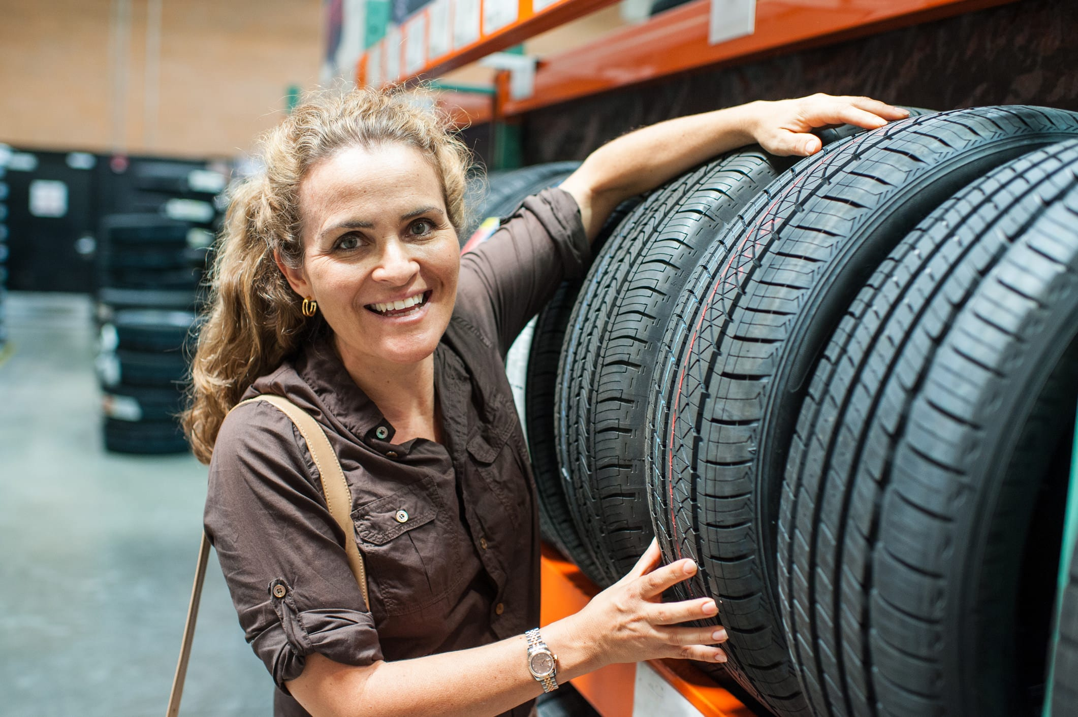 mature smiling caucasian woman shopping for a tire