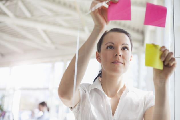 Young businesswoman putting adhesive notes on glass wall in office