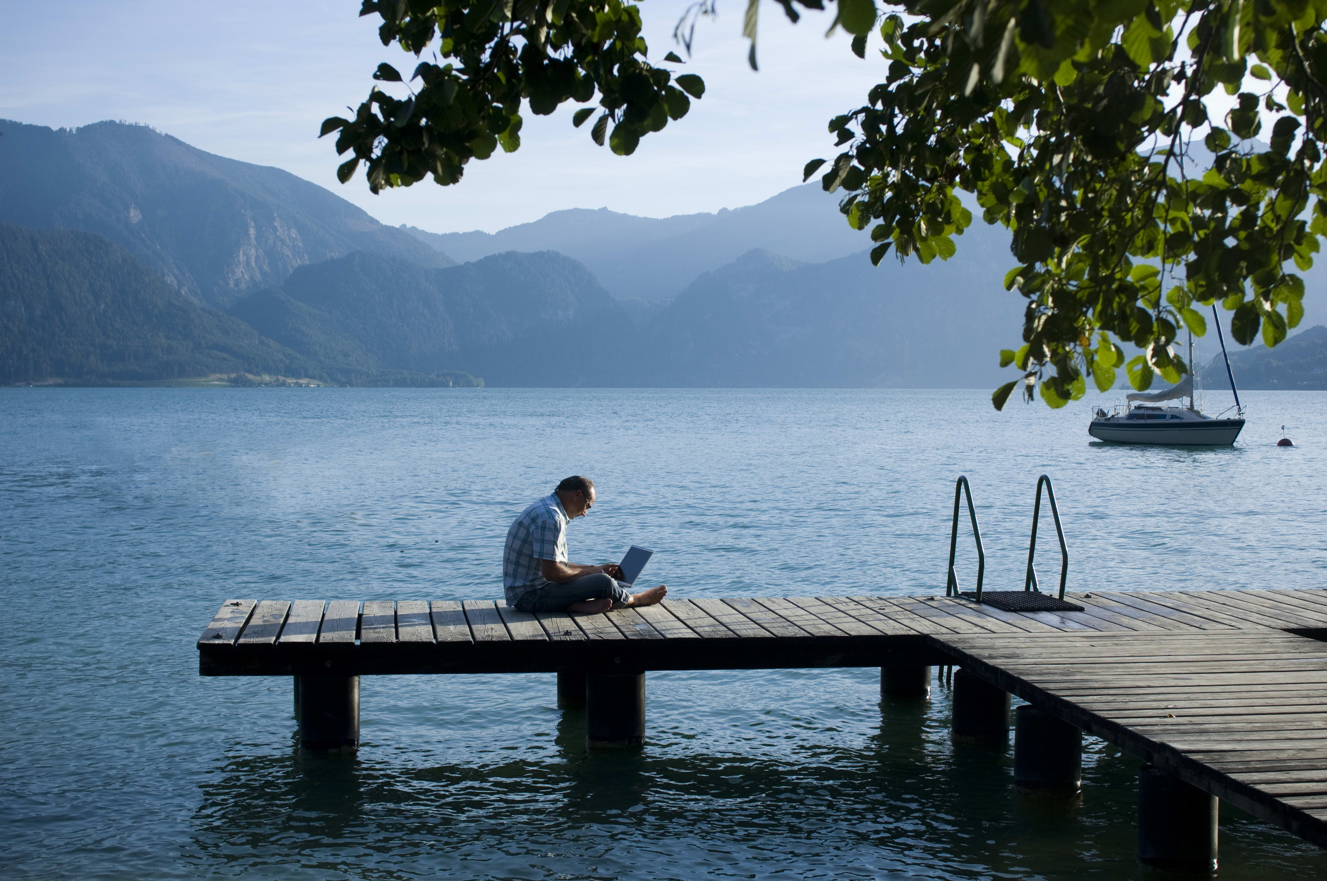 Man with laptop sitting on a jetty