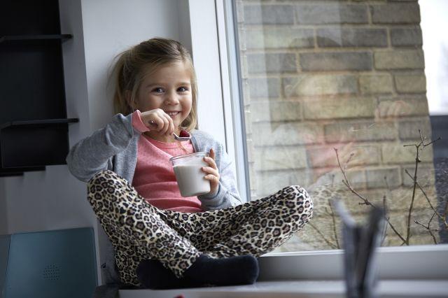 Jente sitter i et vindu og spiser yoghurt