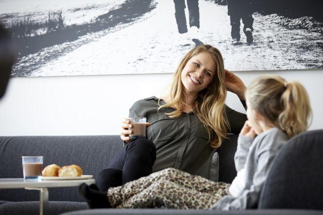 Mor med sjokolademelk og datter i sofa