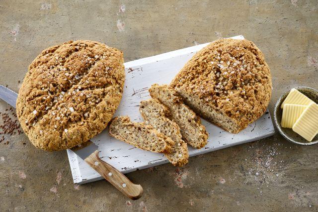 To runde brød med syrnet melk på en fjøl ved siden av en skål med smør i skiver.