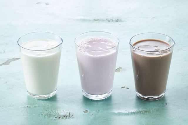 Tre glass melk med smak av jordbær, vanilje og sjokolade