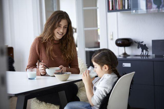 Mor med musliskål og datter med melkeglass