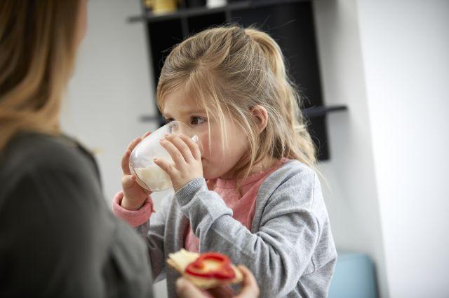 Mor med brødskive og ostepålegg og barn med melkeglass