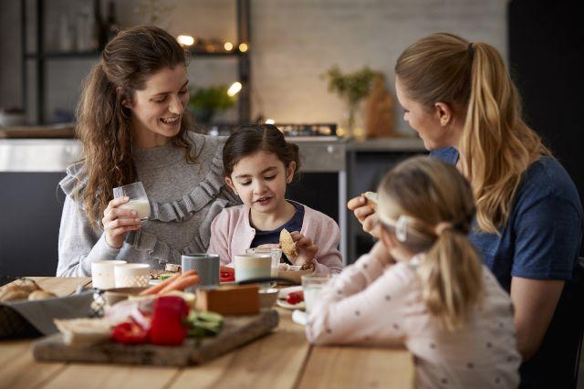 To kvinner og to barn spiser sammen