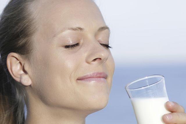 Dame som smiler med lukkede øyne og holder et melkeglass i hånden.