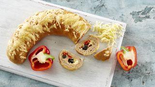 Brød med ost og oliven på en fjøl ved siden av to halve paprika