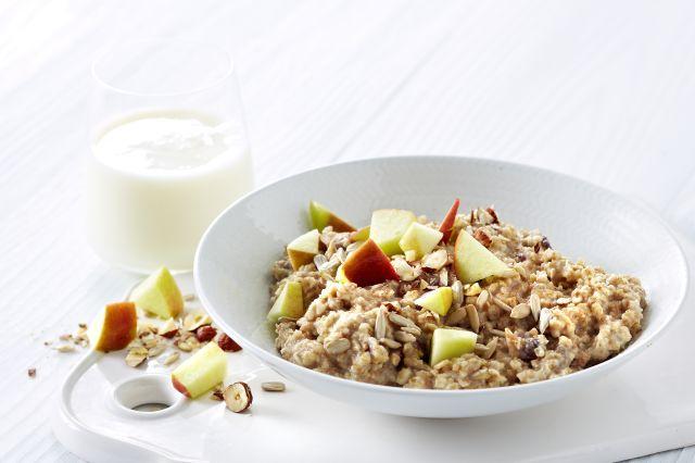Hvetegrøt med eple, nøtter og kanel ved siden av et glass melk
