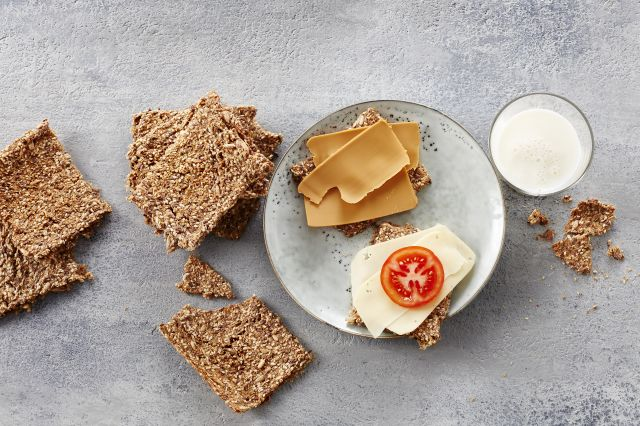 Hjemmelaget knekkebrød med gulost og brunost ved siden av et glass melk