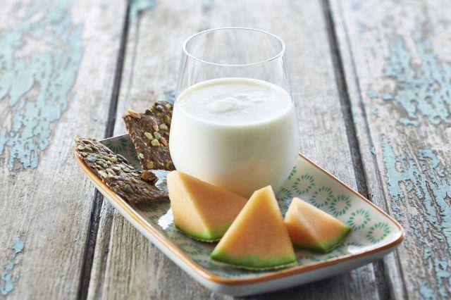 Et melkeglass, noen melonbiter og litt knekkebrød på en tallerken.