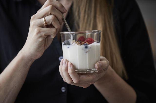 Kvinne spiser yoghurt med bær