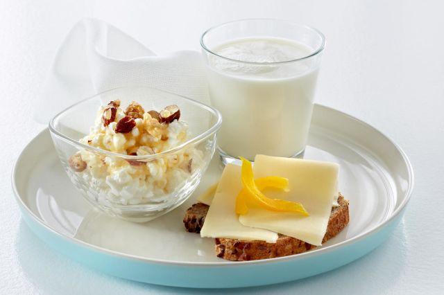 Fat med cottage cheese med syltetøy, en brødskive med gulost og gul paprika og et glass melk.