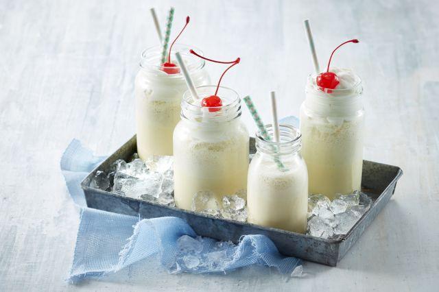 Vaniljeshake i flasker med krem og kirsebær på toppen