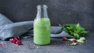 Glassflaske med grønn smoothie med spinat, avokado og yoghurt. Bak flasken ligger det en grå linserviett