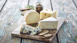 Trefat med fire forskjellige typer oster og kjeks.