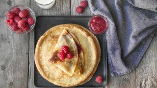 pannekaker toppet med bringebær og et glass melk