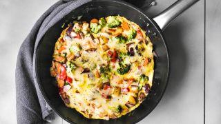 omelett med grønnsaker og ost i en stekepanne