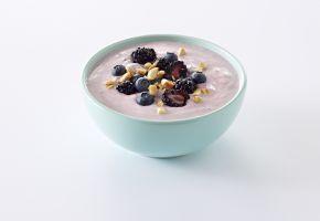 En turkis skål med yoghurt med bær og nøtter.