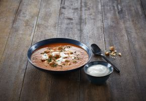 En skål med tomatsuppe med creme fraishe i, og en mindre skål med crème fraîche ved siden av