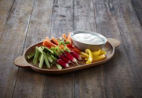 Trebrett med oppskjærte grønnskaer og en skål med lettrømme