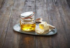 Klaret smør i en krukke, med skiver av smør ved siden av