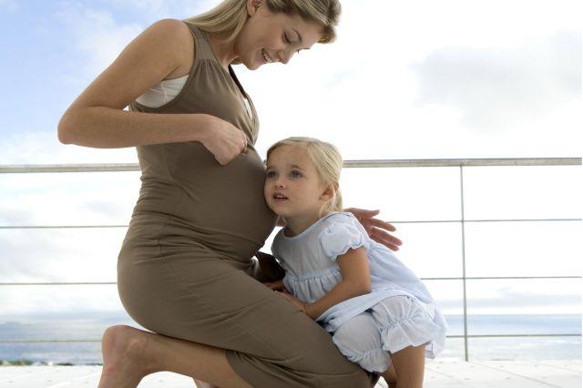 En liten jente som sitter med hodet inntil morens mage. Moren er gravid.