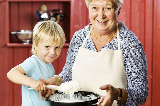 Bestemor som holder opp en kjele med risgrøt, og et barn som rører i grøten med en tresleiv.