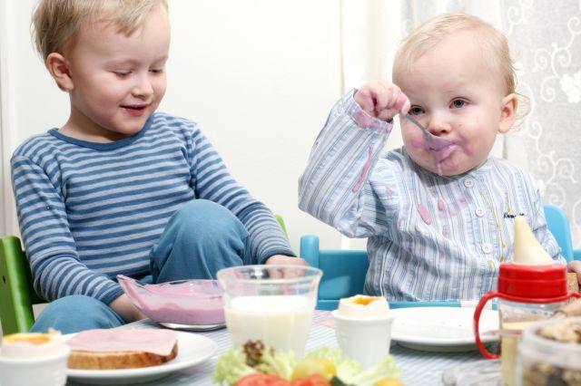 To små gutter som sitter og spiser frokost.