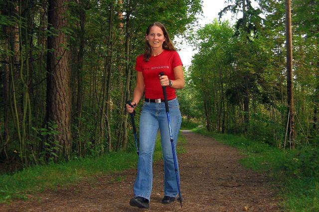 Dame som  går på tur i skogen med staver.