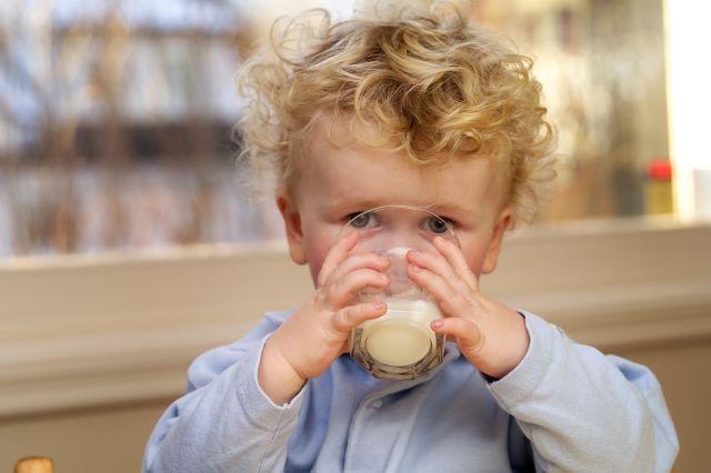 LIten gutt drikker melk av glass.