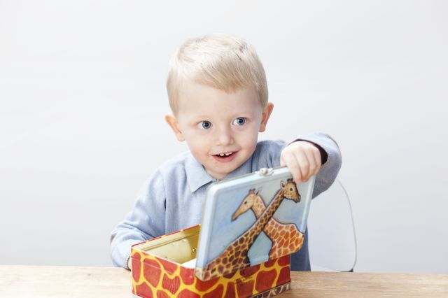 Liten gutt som åpner matboksen sin.