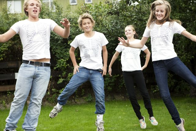 Fire ungdommer med t-skjorter med bilde av skjelett på som hopper og smiler.