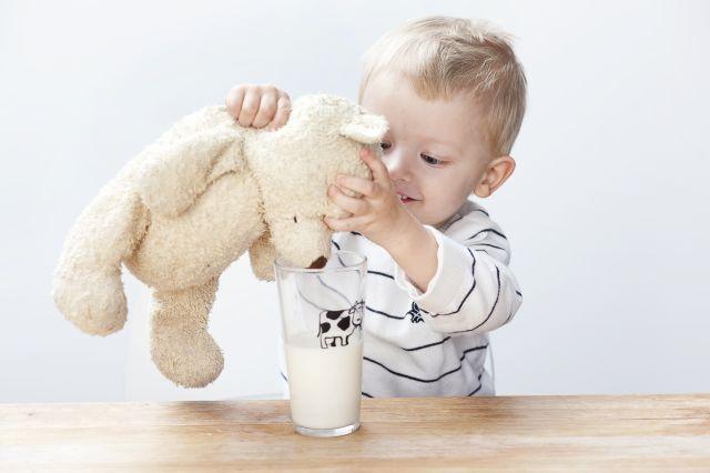 Liten gutt som gir en lysebrun bamse melk fra et glass.