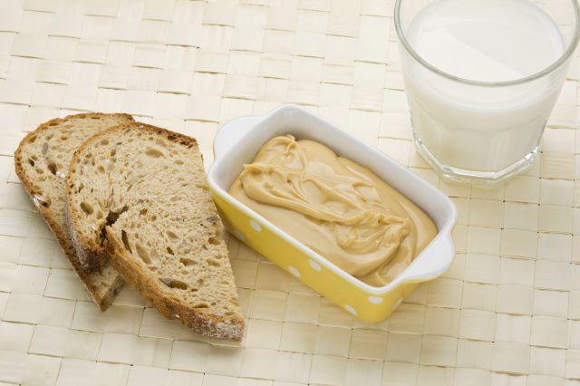 To grove brødskiver, en gul skål med prim og et glass melk på en hvit bordbrikke.