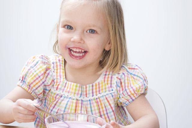 Jente som smiler og spiser yoghurt fra en skål.