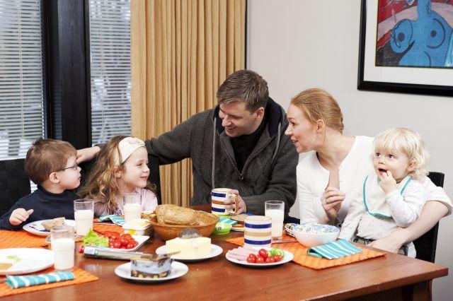 Famile med mor, far og tre små barn som sitter ved et bord og spiser brød og pålegg.