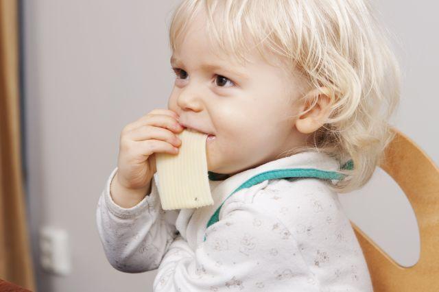 Liten gutt som sitter i en stol og smiler og spiser en skive ost.