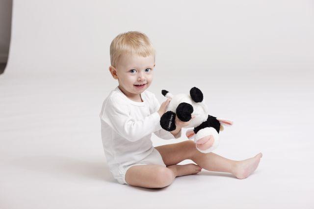 Liten gutt som sitter på gulvet og smiler med en bamse i armene.