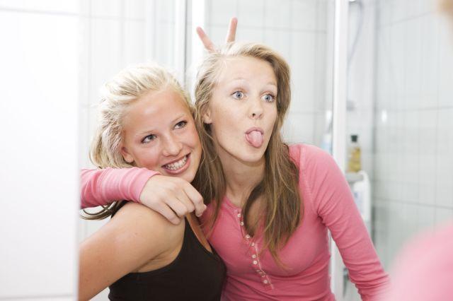 To tenåringsjenter som holder armen rundt hverandre og tuller i speilet.