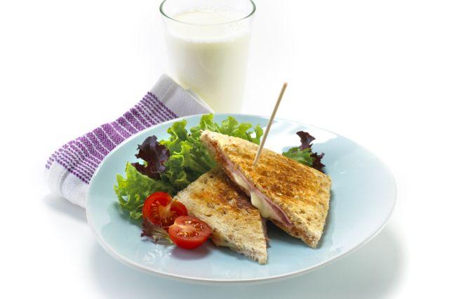Toast og salat på en turkis tallerken med et glass melk.