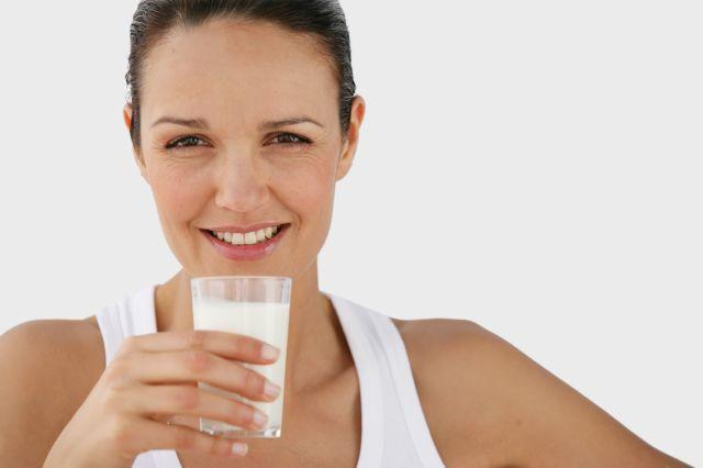Dame som smiler med et glass melk i hånden.