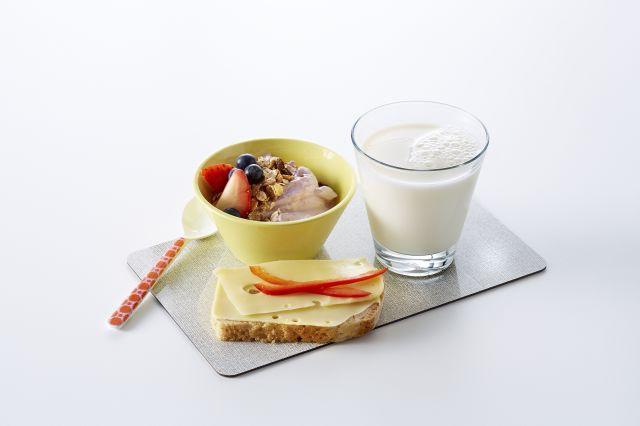 Et melkeglass, en bolle yoghurt med müsli og friske bær og en brødskive med gulost og paprika på en fjøl.